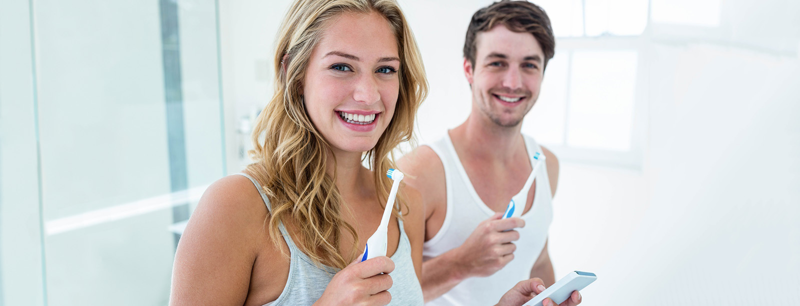Young couple brushing their teeth at home
